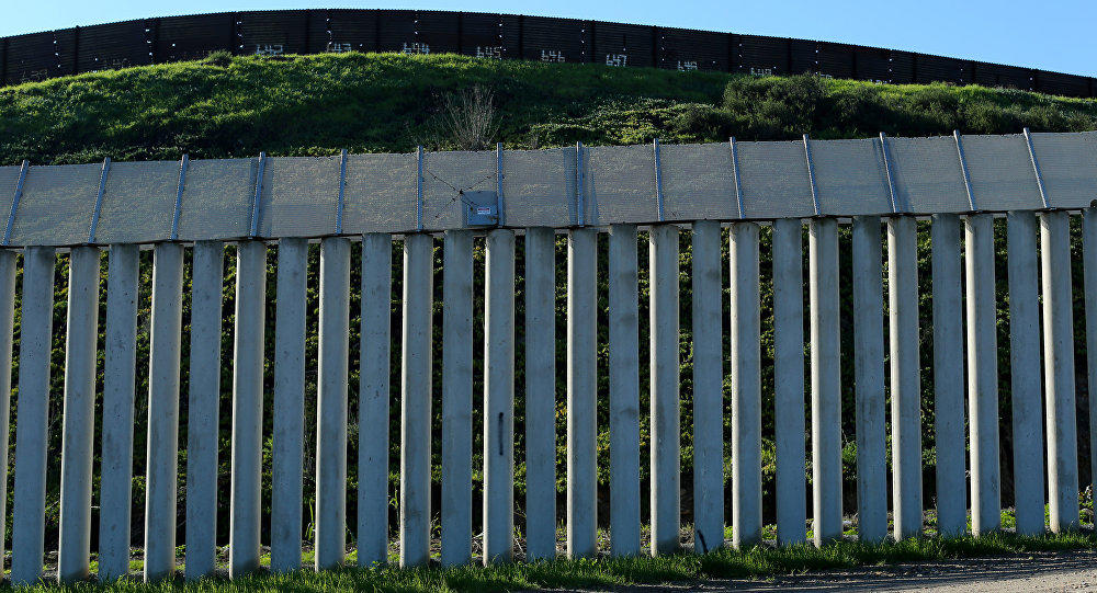 100+ migrants attempt to scale border wall -